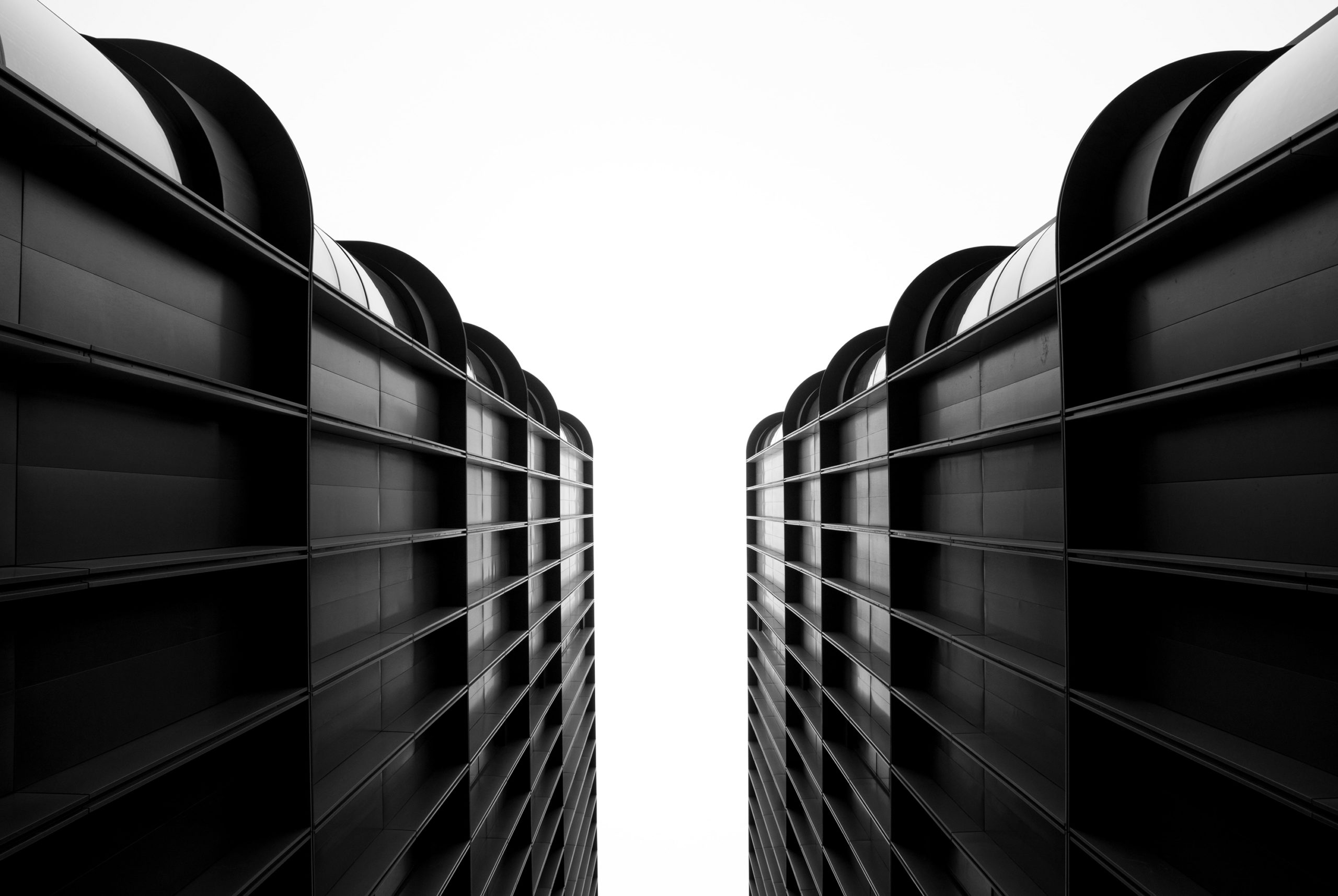 Black and white image between two buildings seen from below.